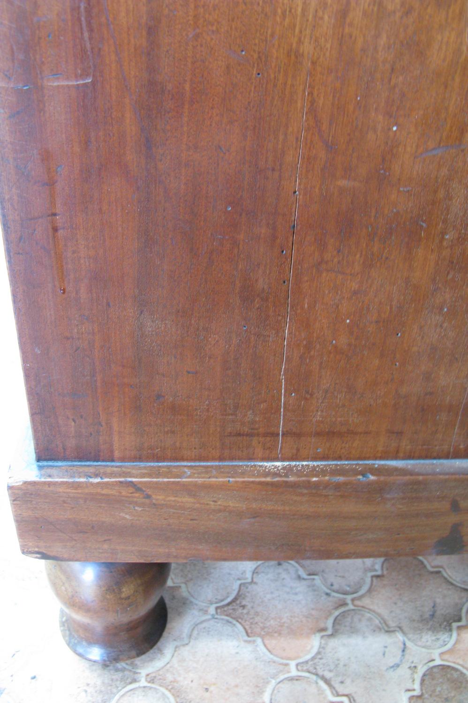 Plinthe abîmée sur le côté droit du secrétaire Empire en placage acajou, avant la restauration.