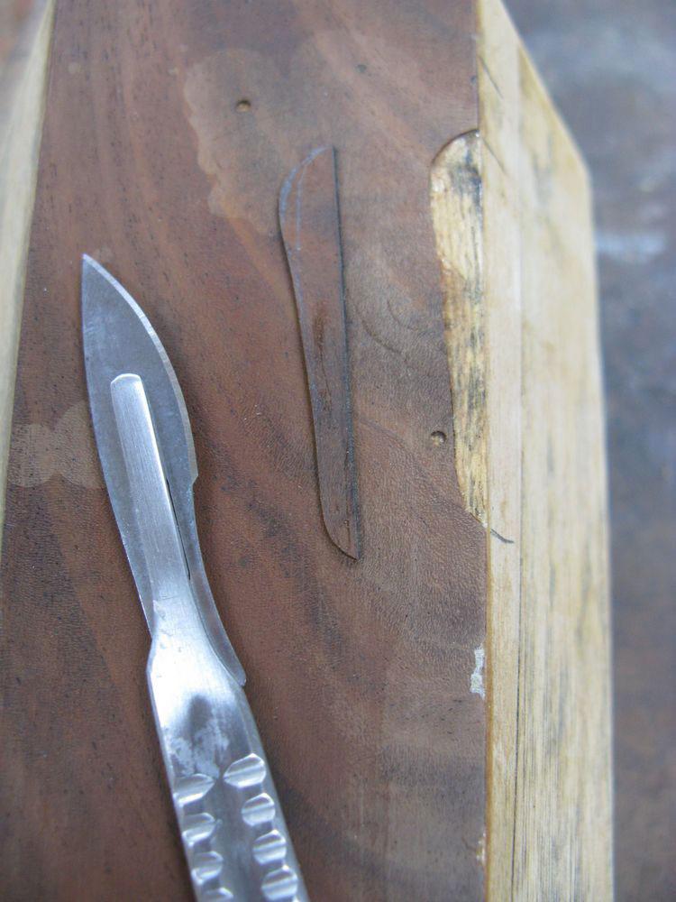 Restauration du placage d'un pied du piano juste sur la lacune.