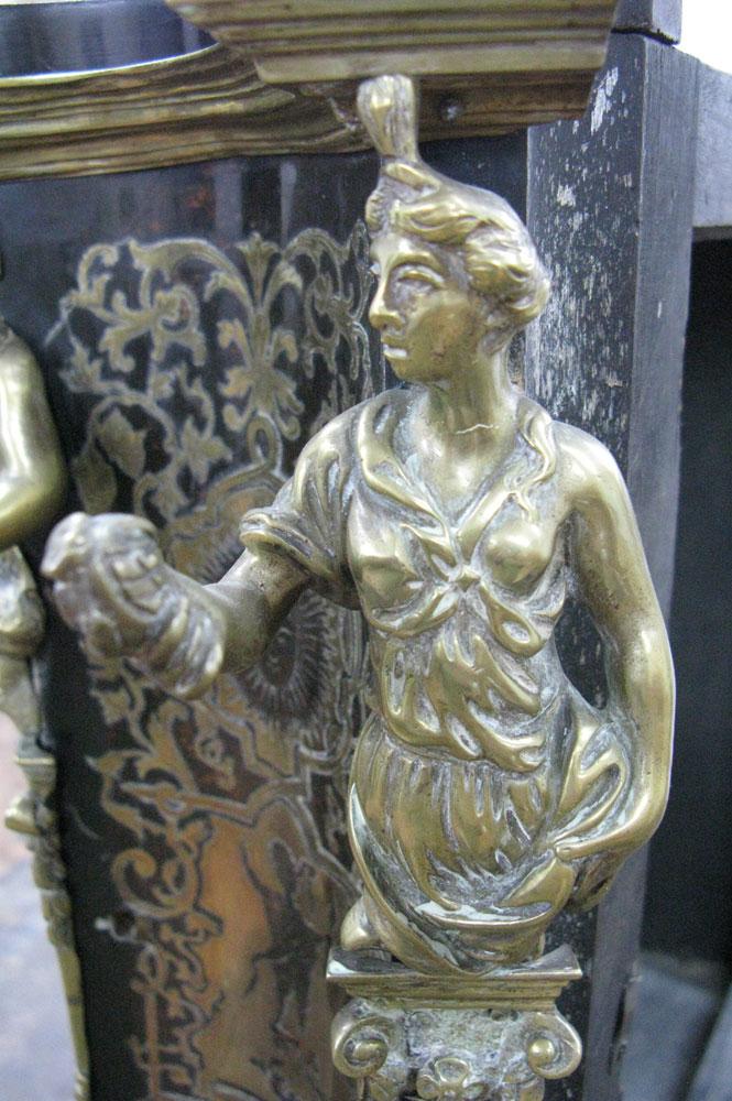 Vue sur la cariatide en bronze avec un fruit dans la main, du côté avant droit du corps principal du cartel Louis XIV avant sa restauration.