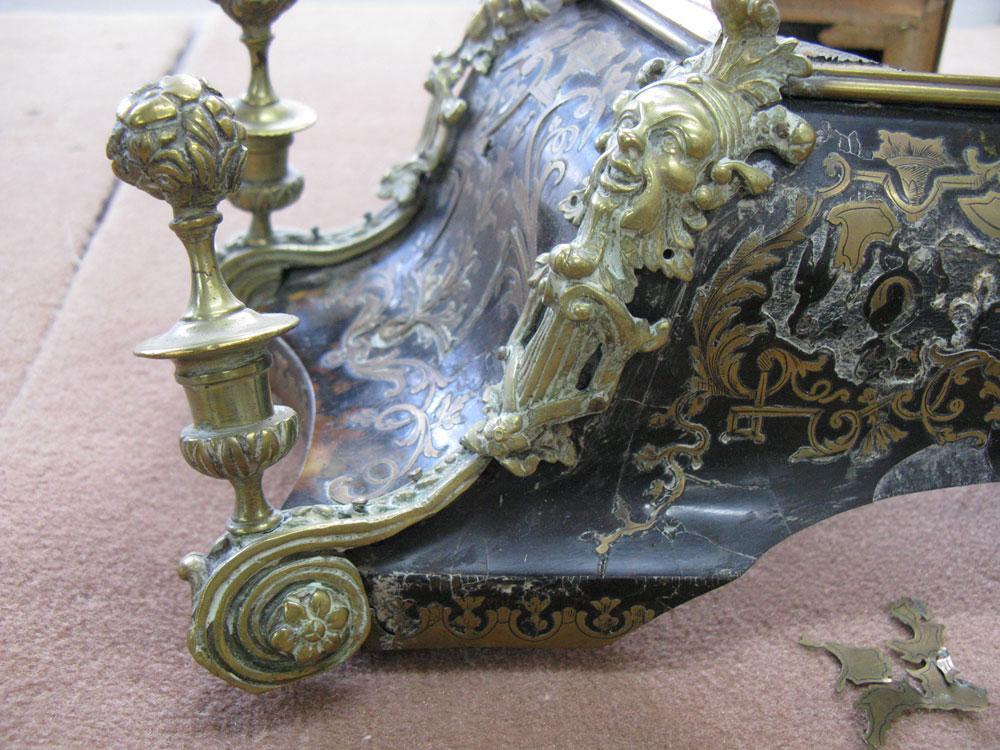 Gros plan de l'angle gauche avec le bronze du chapeau d'amortissement du cartel Louis XIV avant sa restauration.