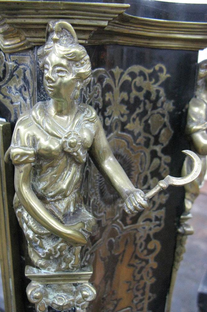 Vue sur la cariatide en bronze tenant une faucille, du côté avant droit du corps principal du cartel Louis XIV avant sa restauration.