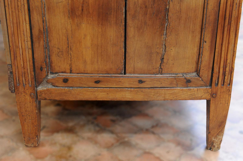 Détail le la moulure inférieure du côté gauche de la commode Louis XVI en merisier avant restauration.
