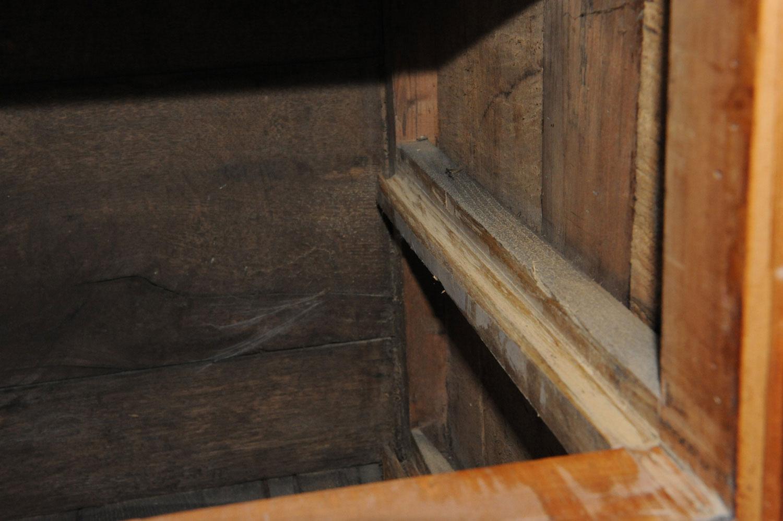 Le coulisseau droit du tiroir de la commode Louis XVI en merisier est usé.
