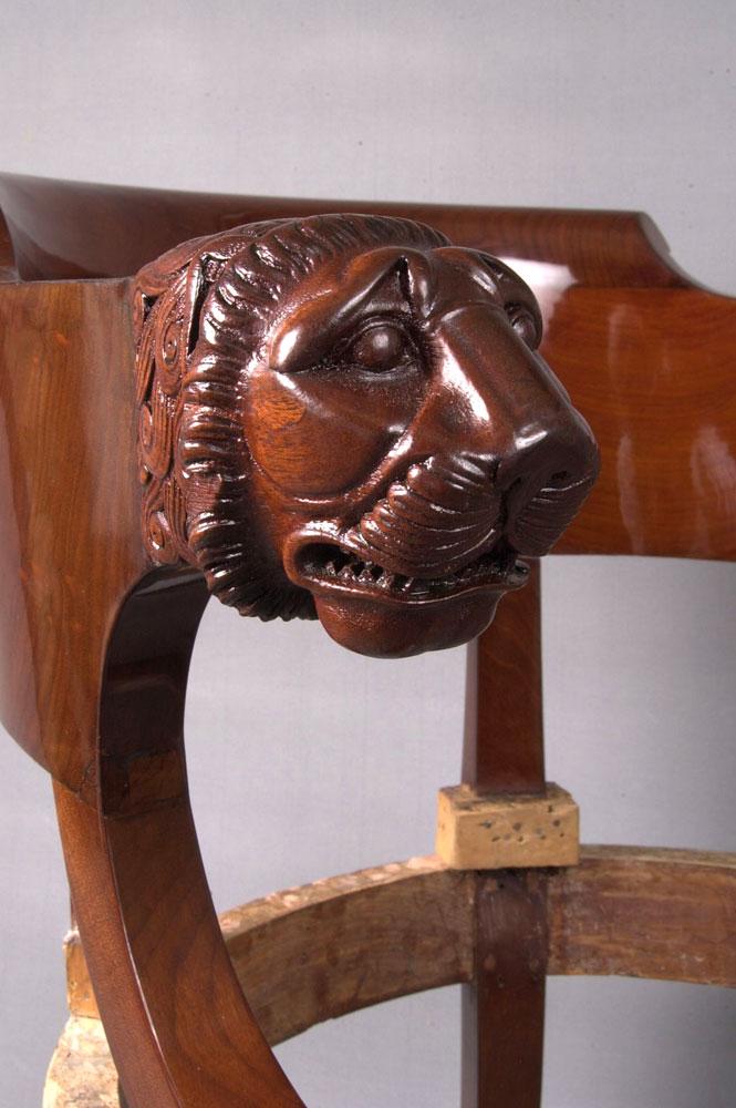 Détail de la sculpture, tête de lion du fauteuil de bureau Empire après restauration.
