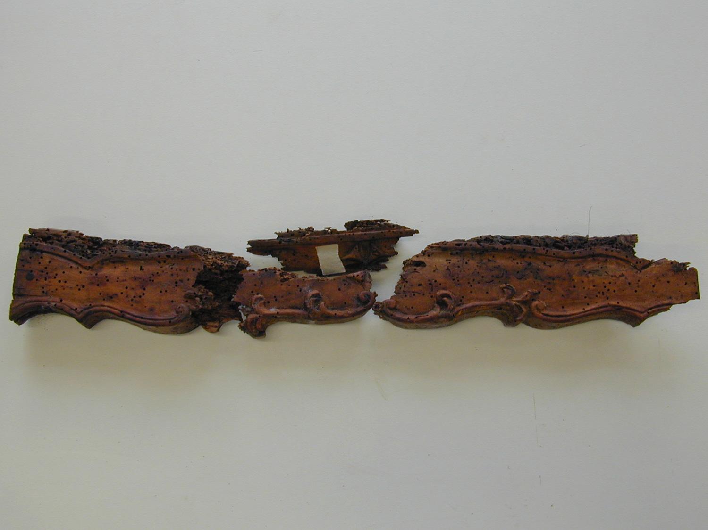 Les quatre morceaux de la traverse de façade du fauteuil Régence après le démontage.