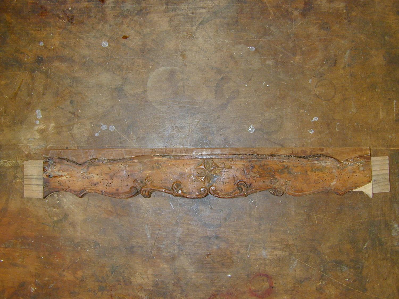 La traverse de façade du fauteuil Régence consolidée et les assemblages restaurés.
