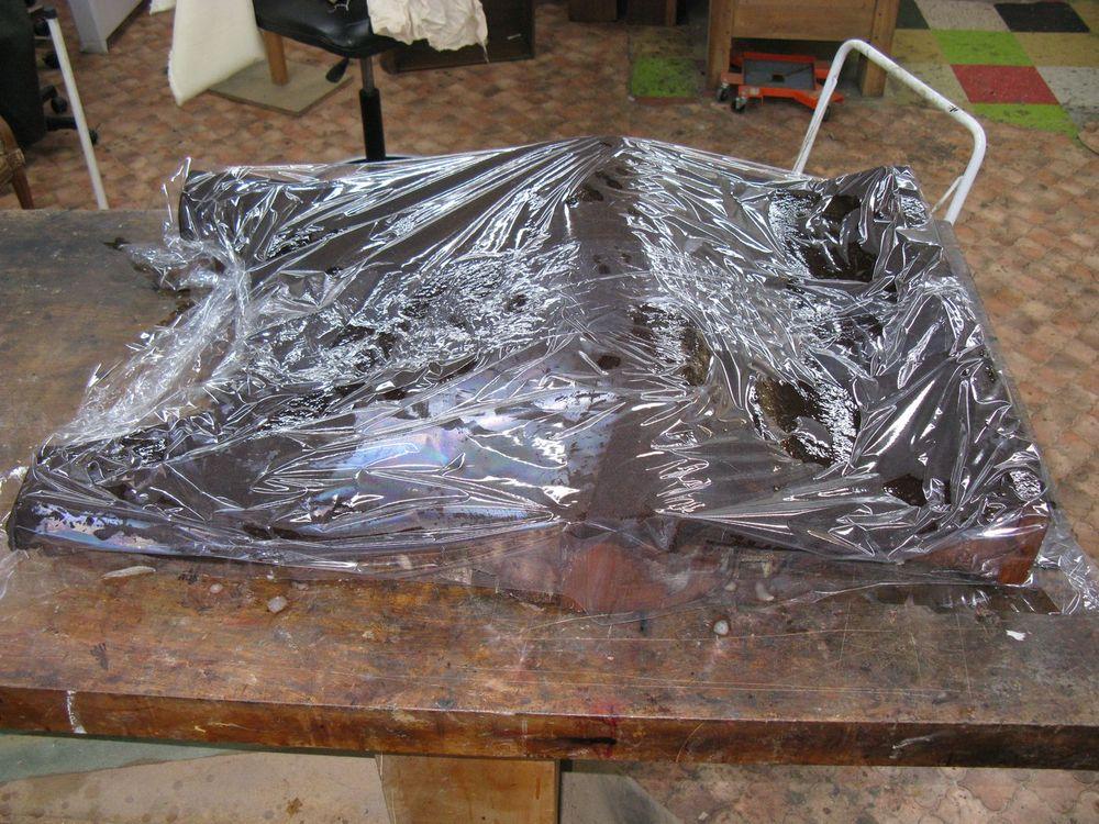 Préparation de la dépose du placage, d'un côté de la commode Régence.