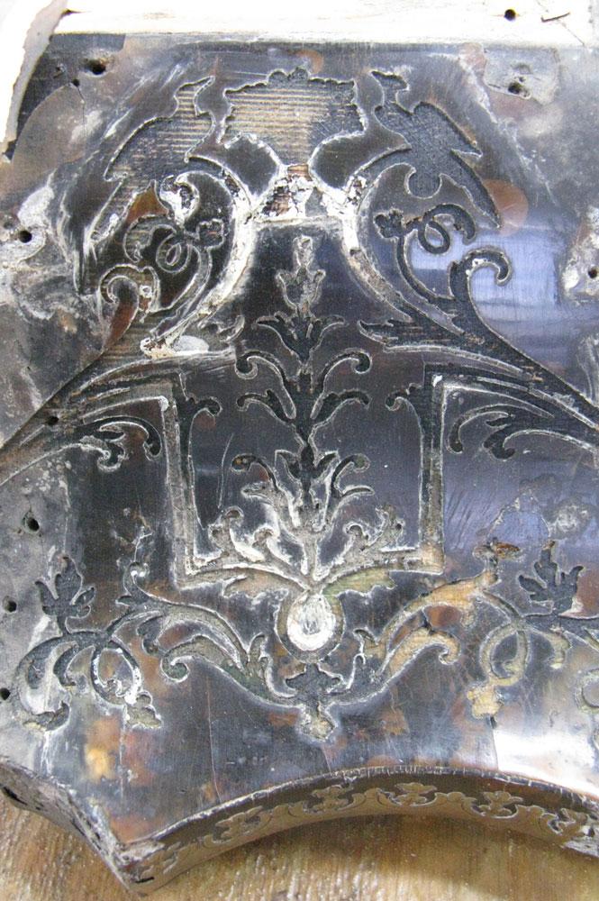 Vue d'un côté du chapeau du cartel Louis XIV dont la marqueterie de laiton a été enlevé.