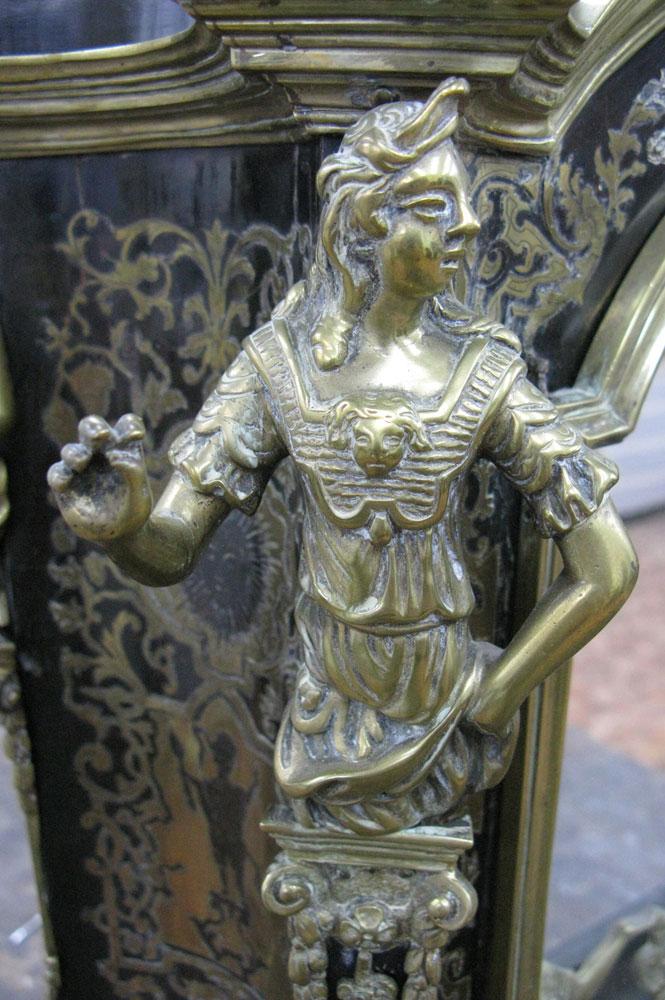 Vue sur la cariatide en bronze du côté avant gauche du corps principal du cartel Louis XIV avant sa restauration.