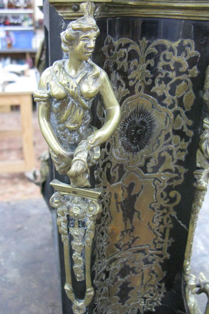 Vue sur la cariatide en bronze avec son socle, du côté arrière gauche du corps principal du cartel Louis XIV avant sa restauration.