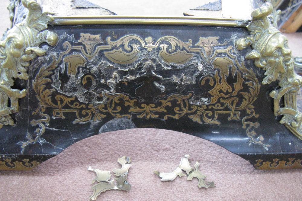 Gros plan sur la façade du chapeau d'amortissement du cartel Louis XIV.