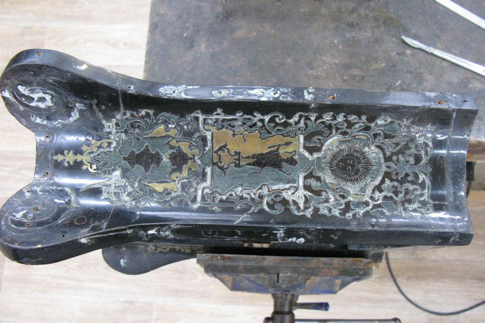 Détail du côté gauche du corps principal en cours de dépose de la marqueterie de laiton.