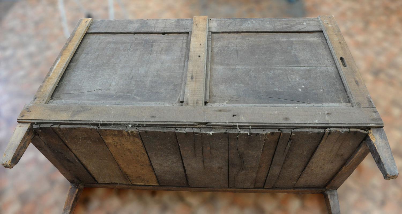 Sur le fond arrière de la commode Louis XVI en merisier, des planches de coffrage ont été pointées.