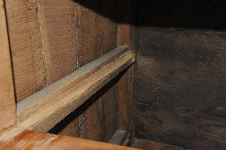 Le coulisseau gauche du tiroir de la commode Louis XVI en merisier est usé.