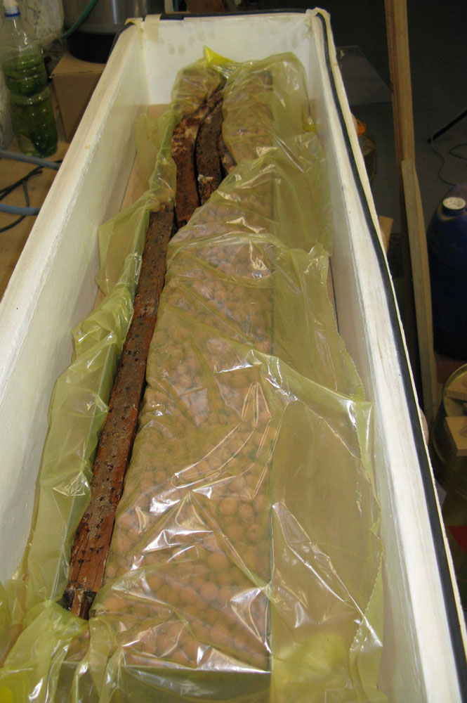 Consolidation des bois de la ceinture du fauteuil de bureau Empire par imprégnation de résine époxyde dans un caisson sous vide.