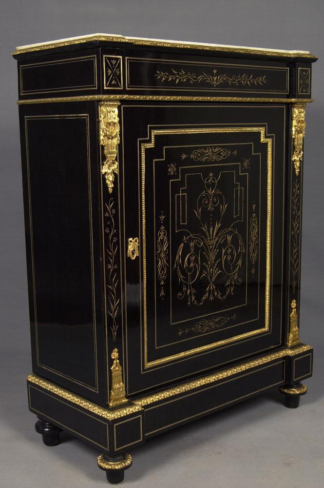 Vue de trois quarts du meuble d'appui Napoléon III en placage d'ébène et gravures dorées après la restauration.