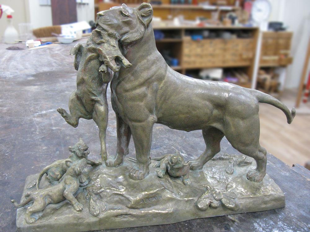 Bronze d'Auguste Cain avant restauration, il représente une lionne tenant dans sa gueule un phacochère, et à ses pieds trois lionceaux crient famine.